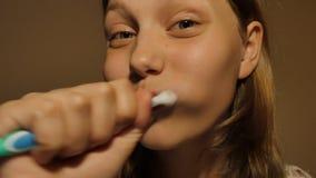 Het tienermeisje borstelt haar tanden, 4K UHD stock videobeelden