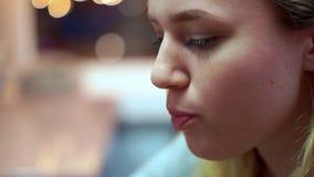 Het tienermeisje drinkt limonade van de buis Zij is in een snel voedselkoffie stock video