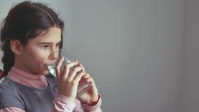 Het tienermeisje drinkt water van een glaskop binnen stock foto