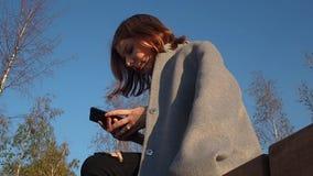 Het tienermeisje in een grijze laag zit in het park en controleert de telefoon op een zonnige dag stock videobeelden