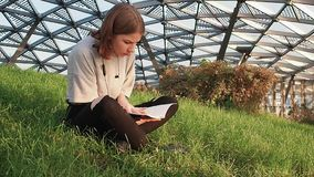 Het tienermeisje in een grijze overhemdszitting op het gras in het park en de lezing een notitieboekje met lezing neemt van op ee stock videobeelden
