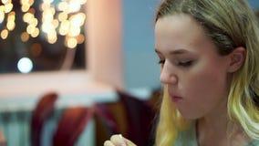 Het tienermeisje eet de kippenstukken in een koffie Zij gebruikt een plastic stop stock video