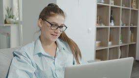 Het tienermeisje gebruikt laptop thuis, het babbelen op sociale netwerken, het glimlachen en het lachen stock footage