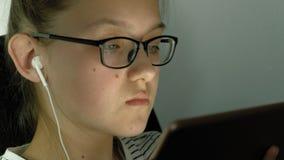 Het tienermeisje gebruikt tablet met hoofdtelefoons Duisternis met verlichting stock footage
