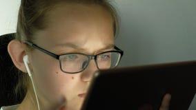 Het tienermeisje gebruikt tablet met hoofdtelefoons Duisternis met verlichting stock videobeelden