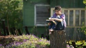 Het tienermeisje leest boekzitting op een stomp in de werf stock footage