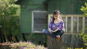 Het tienermeisje leest boekzitting op een stomp in de werf stock videobeelden