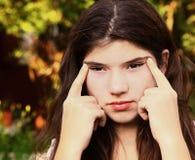 Het tienermeisje met bijziendheid probeert om iets ver weg te zien royalty-vrije stock foto's
