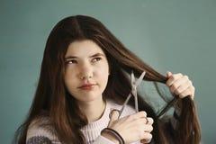 Het tienermeisje met haar haar wordt vermoeid sneed het met schaar die royalty-vrije stock afbeelding