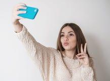 Het tienermeisje met lang haar maakt selfie telefoon stock afbeelding