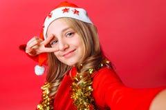 Het tienermeisje toont een groetgebaar en neemt een selfie in Kerstman` s hoed en met klatergoud rond haar hals op een rode achte royalty-vrije stock afbeeldingen