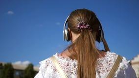 Het tienermeisje in witte kleding met lang haar reist rond de stad tegen de blauwe hemel Langzame Motie Een jong meisje? stock videobeelden