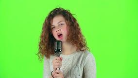Het tienermeisje zingt in retro microfoon vurige liederen Het groene scherm stock footage