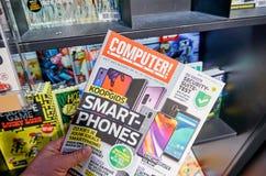 Het tijdschrift van computertotaal in een hand stock foto's