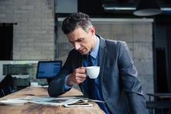 Het tijdschrift van de zakenmanlezing in koffie royalty-vrije stock afbeeldingen