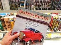 Het tijdschrift van het Roddersdagboek in een hand stock afbeeldingen
