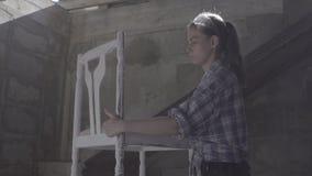 Het timmermansmeisje beëindigt de restauratie van de stoel stock video