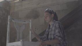 Het timmermansmeisje herstelt en assembleert een stoel stock video