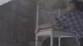 Het timmermansmeisje herstelt en assembleert een stoel stock footage