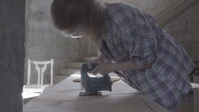 Het timmermansmeisje maakt de stoelzetel uit triplex gebruikend een elektrische figuurzaag stock videobeelden