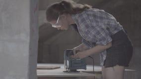 Het timmermansmeisje maakt de stoelzetel uit triplex gebruikend een elektrische figuurzaag stock video