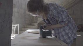 Het timmermansmeisje maakt de stoelzetel uit triplex gebruikend een elektrische figuurzaag stock footage