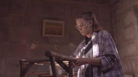 Het timmermansmeisje werkt in de workshop, hersteld uitstekend meubilair stock footage