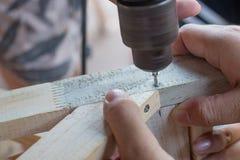 Het timmermanswerk, Boor houten raad met elektrische boor, Stock Foto