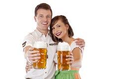 Het toejuichen van de man en van de vrouw met meest oktoberfest bierstenen bierkroes royalty-vrije stock foto