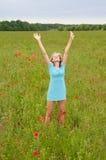 Het toejuichen van de vrouw op papavergebied Stock Afbeelding