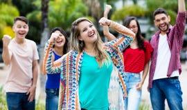 Het toejuichen van Duits meisje met gelukkige groep vrienden stock afbeeldingen