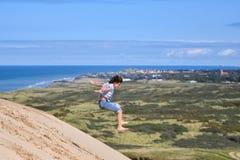 Het toejuichen van het gelukkige en blije Aziatische vrouw springen van rand van de berg de piekklip, Denemarken stock foto's