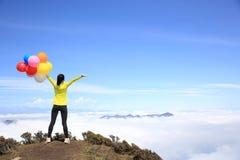Het toejuichen van jonge vrouw met kleurrijke ballons op bergpiek Stock Foto's