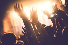Het toejuichen van menigte met dient lucht bij muziekfestival in stock foto
