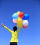 Het toejuichen van vrouw het lopen met kleurrijke ballons op bergpiek Stock Afbeelding