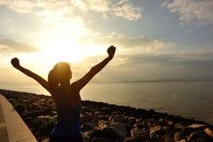 Het toejuichen van vrouwen open wapens op strand Royalty-vrije Stock Afbeelding
