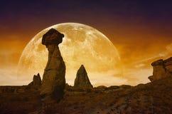 Het toenemen bloedige rode volle maan, silhouetten van paddestoelrotsen Stock Afbeeldingen