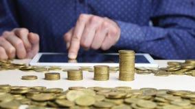 Het toenemen kolommen van muntstukken Het mensenwerk aangaande de digitale tablet stock videobeelden