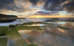 Het toenemen zon op Turrimetta-kustlijn Sydney Stock Foto's
