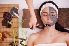 Het toepassen van gezichtsmasker bij vrouwengezicht bij schoonheidssalon stock afbeelding