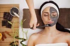 Het toepassen van gezichtsmasker bij vrouwengezicht bij schoonheidssalon Stock Foto's