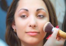 Het toepassen van gezichtspoeder op een mooi meisjesgezicht Stock Afbeeldingen
