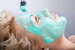 Het toepassen van het pak van het moddergezicht op vrouwengezicht royalty-vrije stock fotografie