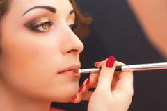Het toepassen van lippenproducten op een vrouwengezicht Stock Foto's