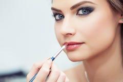 Het toepassen van lippenstift met een borstel royalty-vrije stock foto's