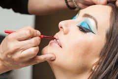 Het toepassen van lippenstift op een witte vrouw royalty-vrije stock afbeeldingen