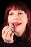 Het toepassen van lippenstift op heerlijke lippen stock afbeeldingen