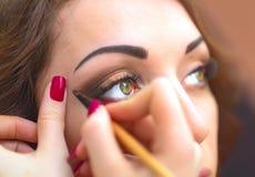 Het toepassen van make-up, eyeliner op een mooi van de leeftijd afhankelijk vrouwengezicht Stock Foto's