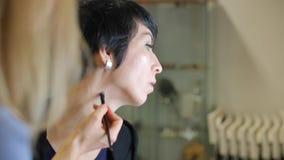 Het toepassen van make-up op een pukkelhals stock videobeelden
