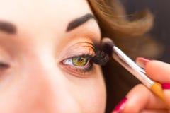 Het toepassen van oogschaduw op ooglid Stock Foto